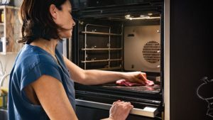 Image of a woman cleaning the inside of an integrated oven appliance